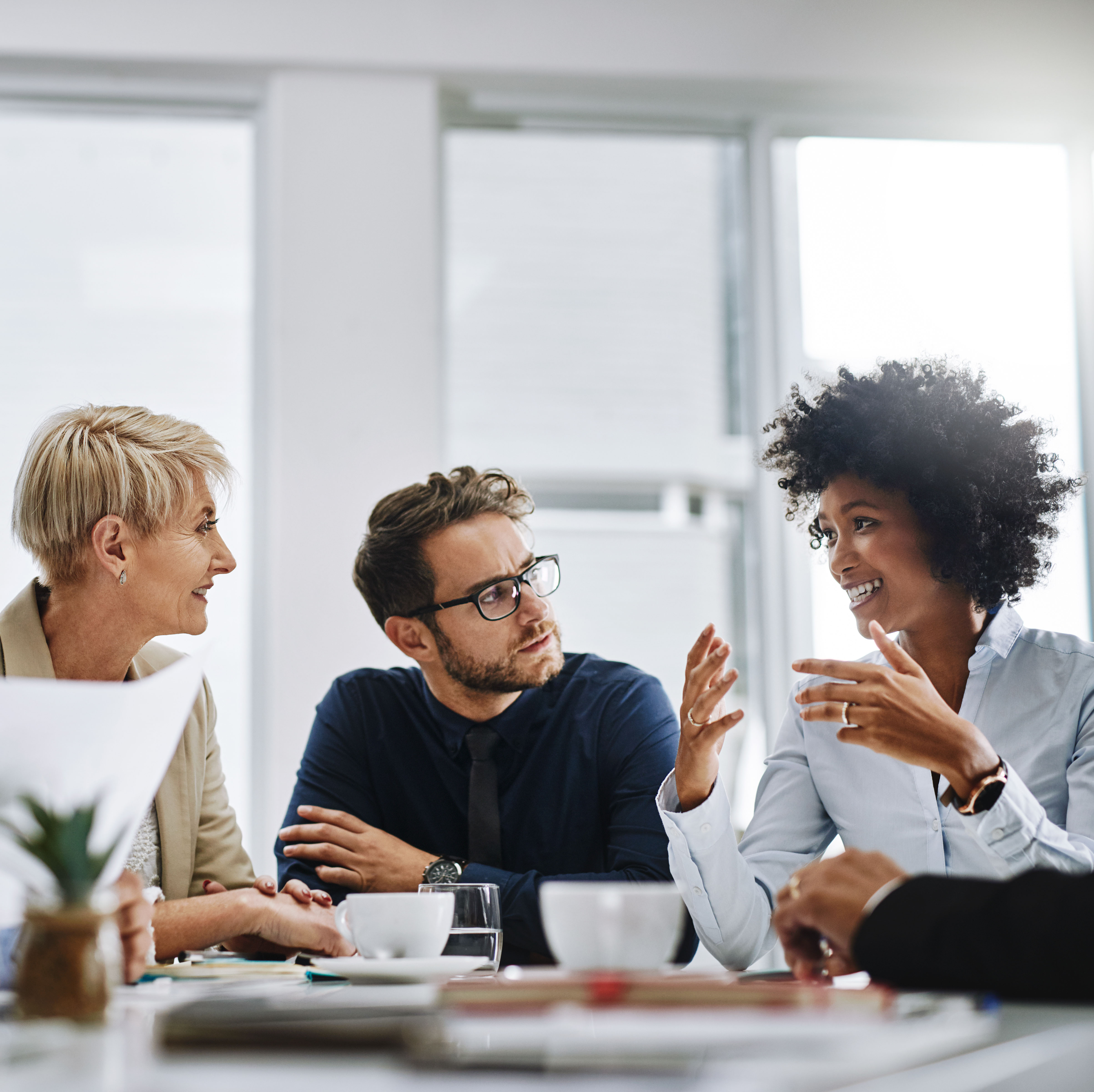 Three professionals having a conversation in a work environment
