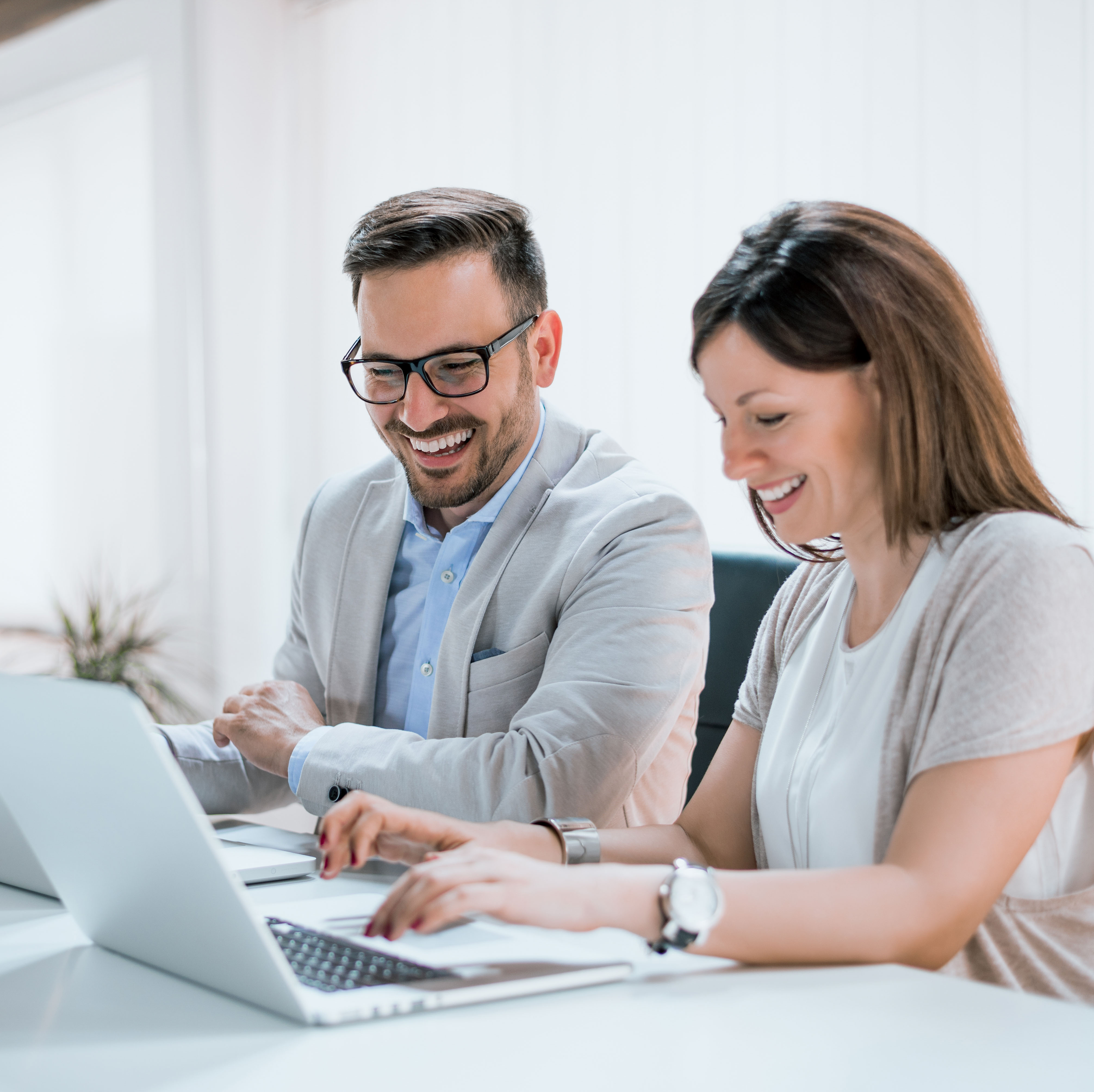 Two people smiling while working on their laptops