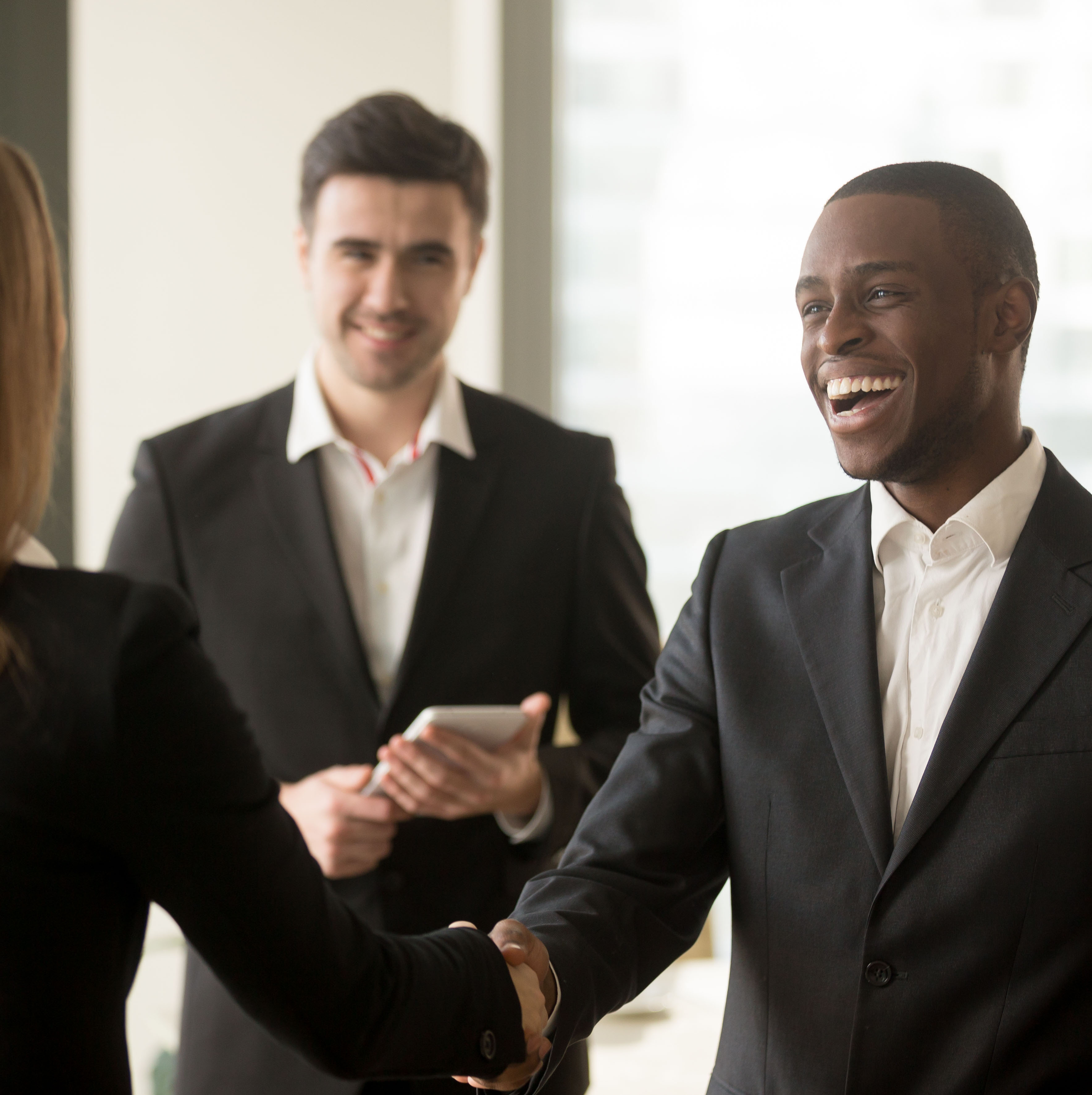 A person smiling and shaking someones hand while another person smiles in the background