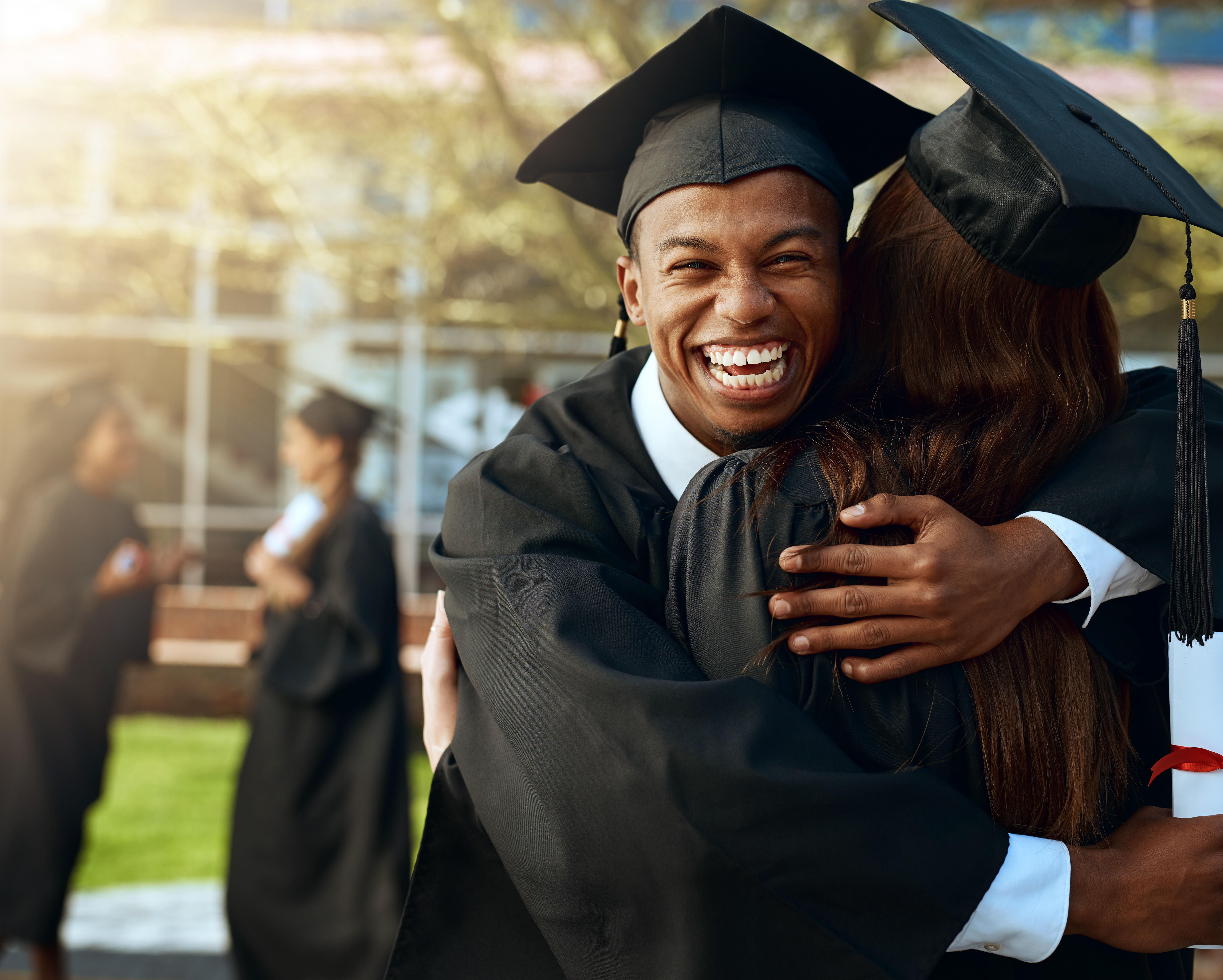 Student in a graduation cap and gown hugging someone and smiling at the camera